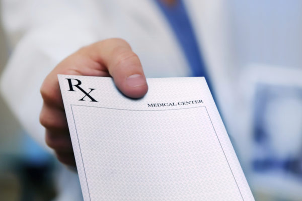 doctor holding out blank prescription pad